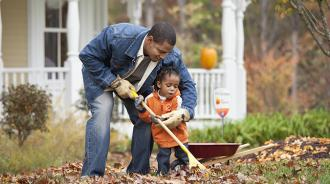 Dad and child raking leaves
